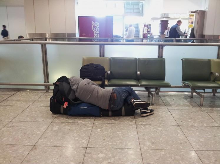 Viajante tira um cochilo no aeroporto de Heatrow, em Londres. Foto: Giuseppe Galli.