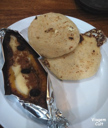 As pupusas são as da direita. Do lado esquerdo, banana assada com creme e passas